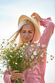 Beautiful woman in hat and with a basket of field daisies in sunny summer day
