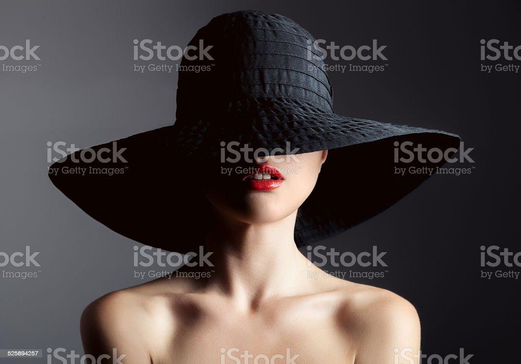 Beautiful woman in hat. Retro fashion. Dark Background. stock photo