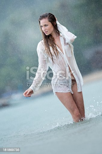 Beautiful woman walking through the ocean shore in the middle of heavy Monsoon Rain.