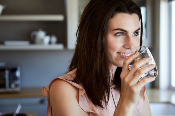 beautiful woman in kitchen - drinking water stock photos and pictures