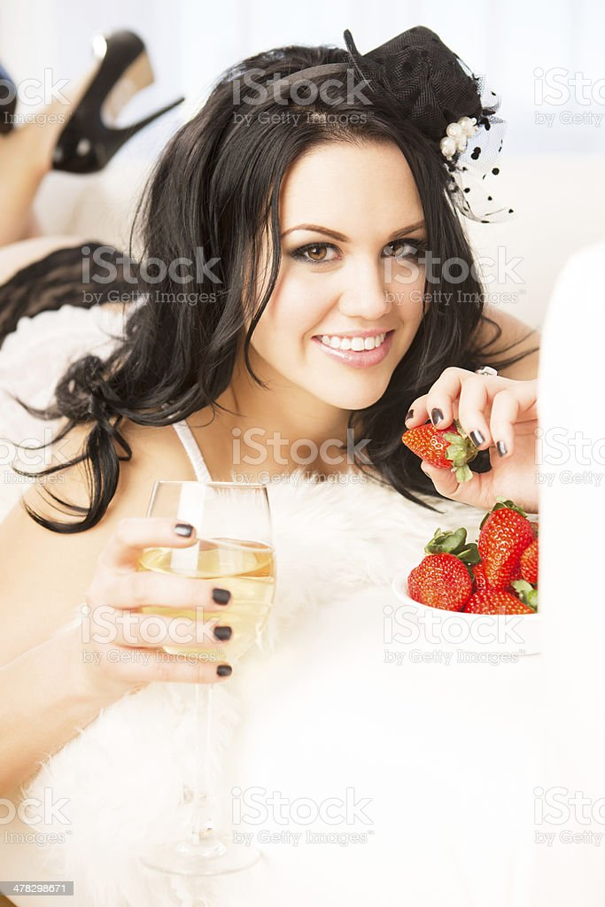 Beautiful woman in lingerie eating strawberries royalty-free stock photo