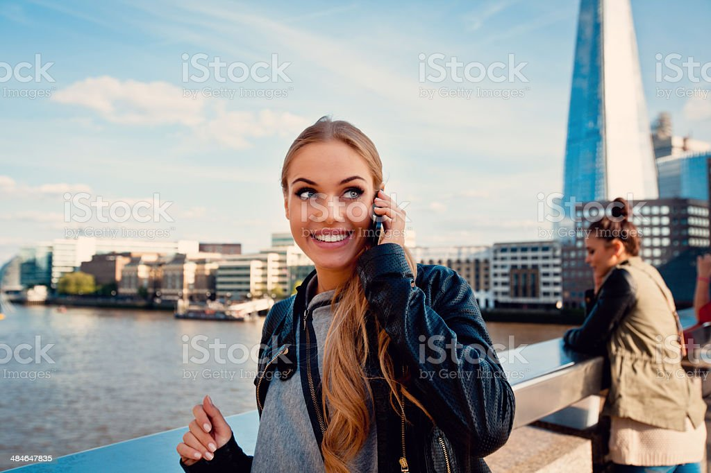 Beautiful woman in London Outdoor portrait happy young woman talking on phone with The Shard Tower in the background. 20-24 Years Stock Photo