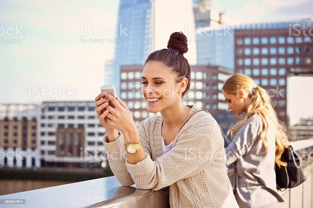 Beautiful woman in London Outdoor portrait happy young woman using the smart phone with The Shard Tower in the background. 20-24 Years Stock Photo