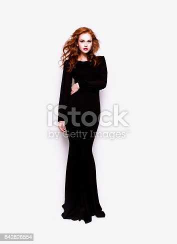 Portrait of young beautiful redhead woman with professional make-up looking gorgeous wearing luxury long black dress on white background