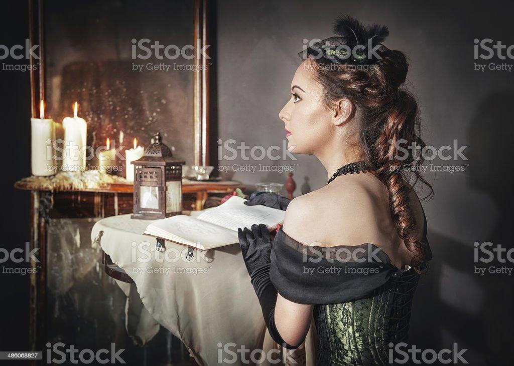 Beautiful woman in medieval dress near mirror stock photo