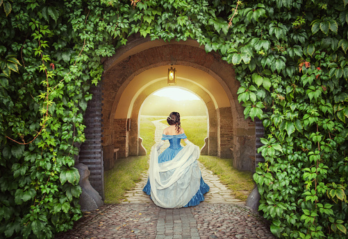 Beautiful woman in medieval dress on the mysterious road
