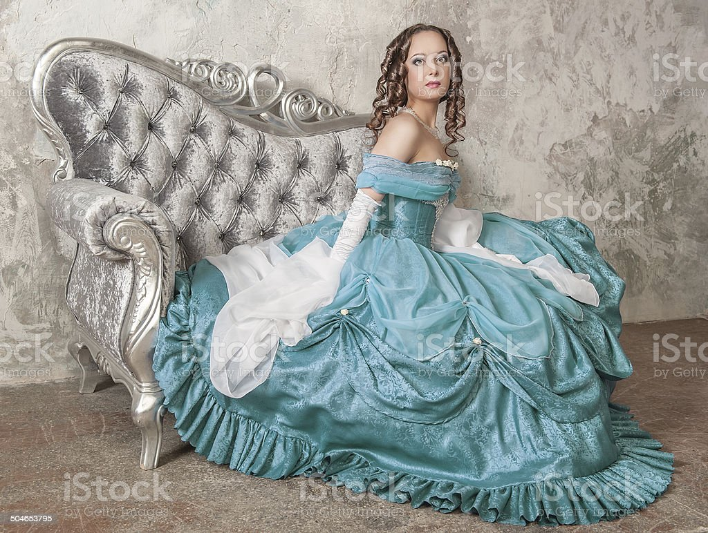 Beautiful woman in medieval dress on the sofa stock photo