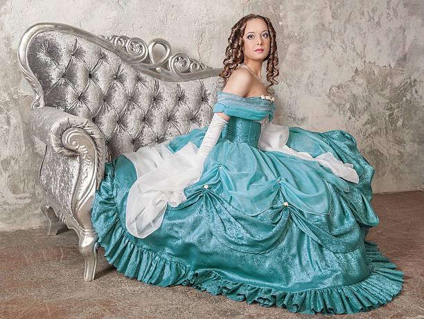 schöne frau in mittelalterlichen kleid auf dem sofa - prinzessinnenstil stock-fotos und bilder