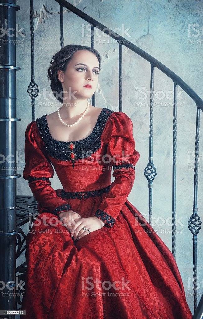 Beautiful woman in medieval dress on the stairway stock photo