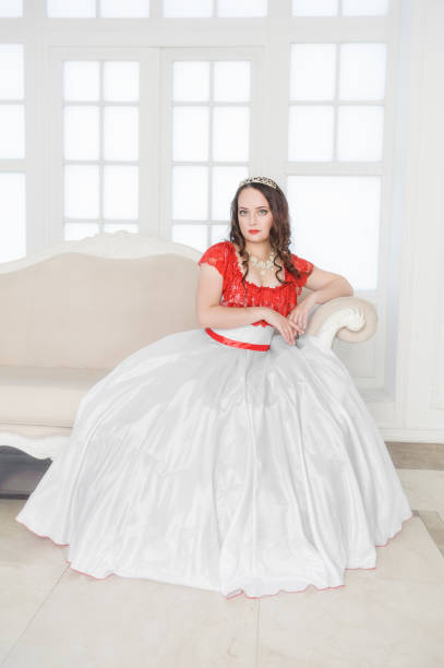 beautiful woman in medieval dress sitting on the sofa - petticoat stock pictures, royalty-free photos & images