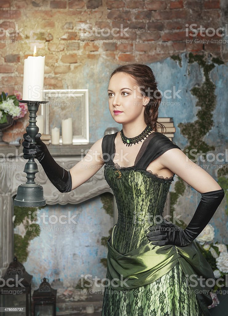 Beautiful woman in medieval dress with burning candle stock photo