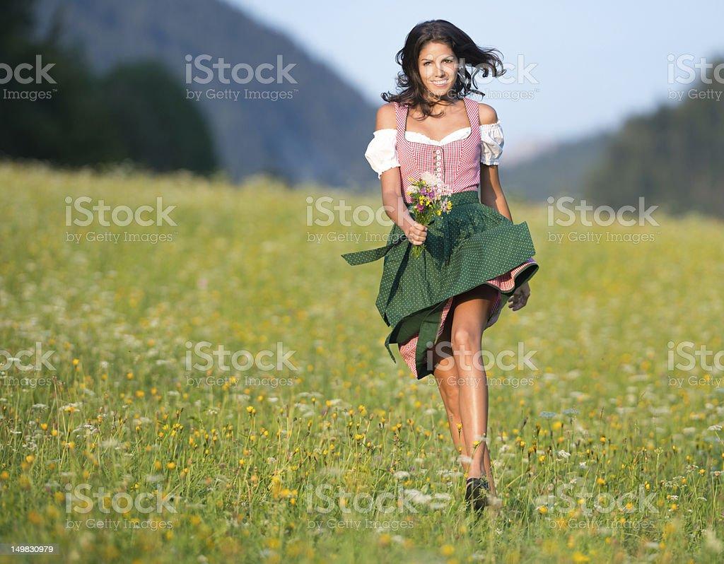 Beautiful woman in Oktoberfest Dirndl Fashion running through the Meadows stock photo