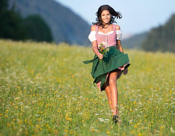 schöne frau in oktoberfest dirndl mode, die durch die meadows - bayerische tracht stock-fotos und bilder