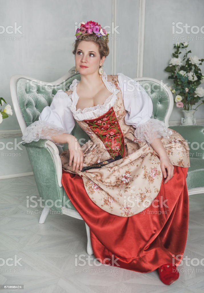 Beautiful woman in old-fashioned medieval dress on the sofa stock photo