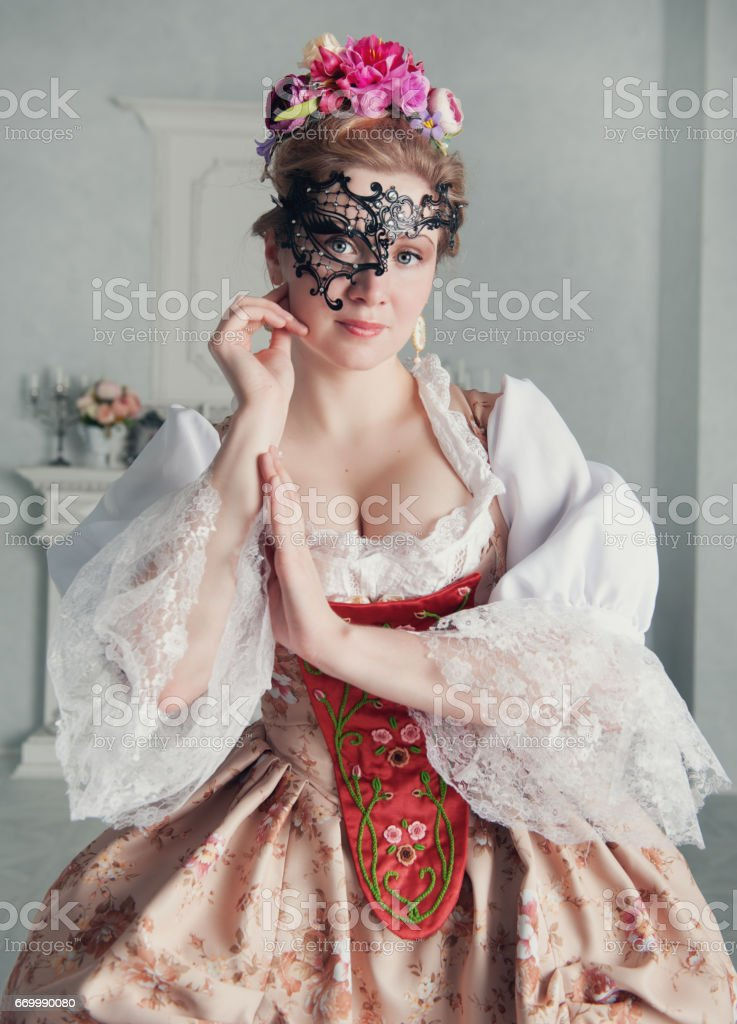 Beautiful woman in old-fashioned medieval dress with mask stock photo