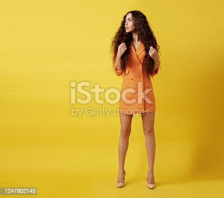 Beautiful woman in orange jacket standing front of yellow background.