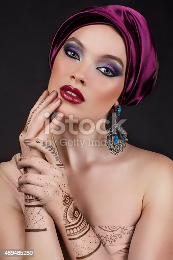 istock beautiful woman in oriental style with mehendi in hijab 489485280