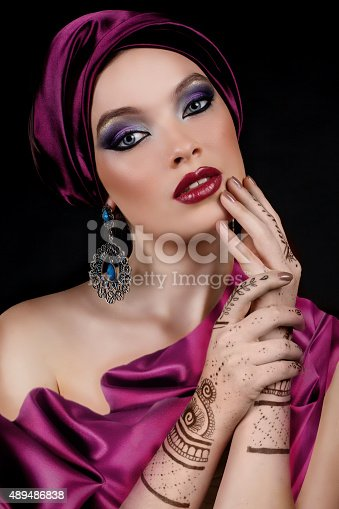 istock beautiful woman in oriental style with mehendi in hijab 489486838