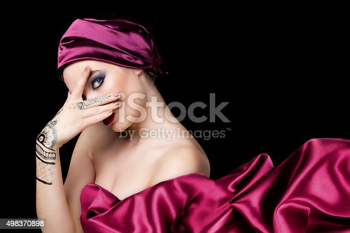 istock beautiful woman in oriental style with mehendy in hijab 498370898