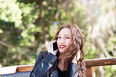 istock Beautiful woman in park with smart phone 624853288