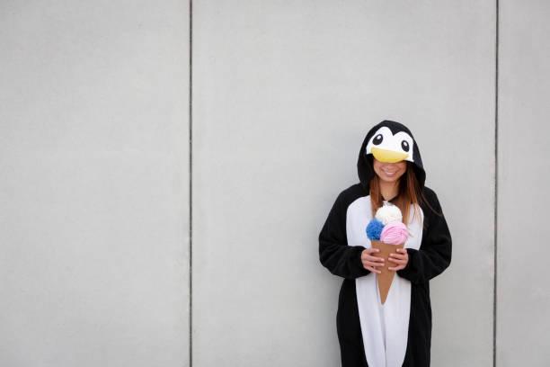 schöne Frau in Pinguin Kostüm isst Dekoration Eis – Foto