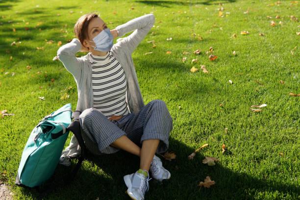 Bela mulher com máscara protetora sentada em parque solitário - foto de acervo