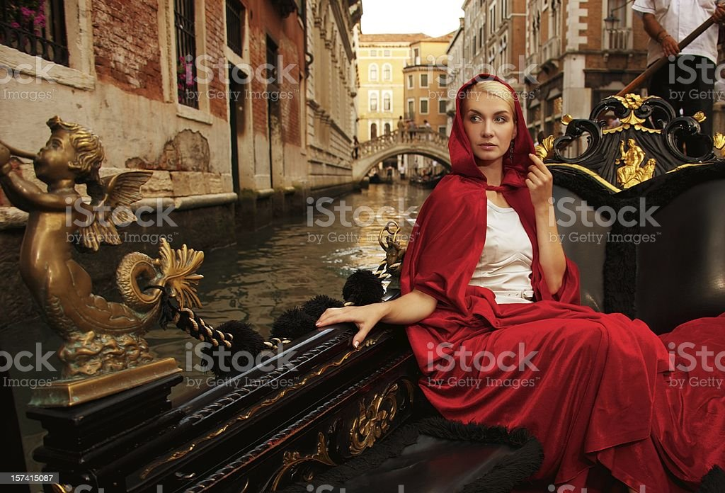 Beautiful woman in red cloak riding on gandola stock photo