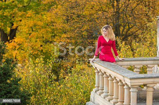 istock Beautiful Woman in red dress and old arhitecture on Fall Nature Background 866657658