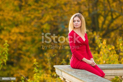 istock Beautiful Woman in red dress and old arhitecture on Fall Nature Background 866657666