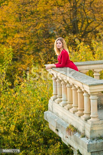 istock Beautiful Woman in red dress and old arhitecture on Fall Nature Background 866657778