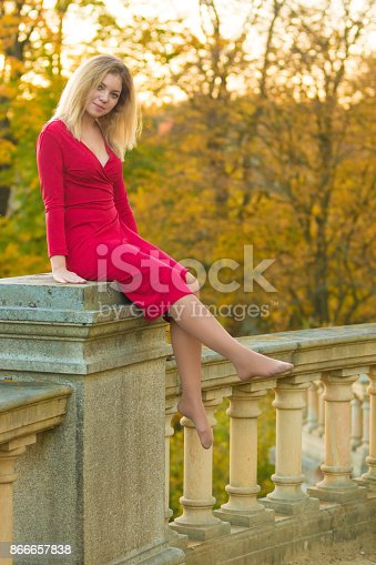 istock Beautiful Woman in red dress and old arhitecture on Fall Nature Background 866657838