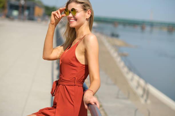 빨간 드레스에 아름 다운 여자입니다. 도시 강 배경입니다. 스톡 사진