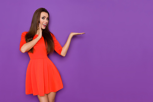 istock Beautiful Woman In Red Dress Is Holding Hand On Chin, Talking And Presenting 924899664