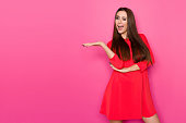 istock Beautiful Woman In Red Dress Is Winking, Talking And Presenting 899696452