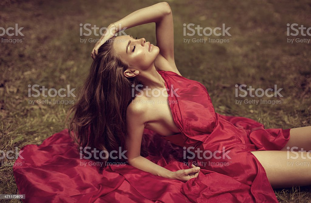 Beautiful woman in red dress lying on the grass stock photo