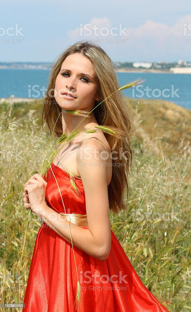 beautiful woman in red dress near the sea royalty-free stock photo