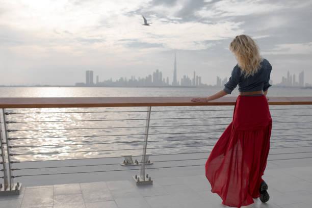 schöne frau im roten kleid auf dem hintergrund des meeres. - hochzeitsreise dubai stock-fotos und bilder