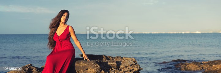 istock Beautiful woman in red dress sitting on the cliffs beside the sea 1064350700
