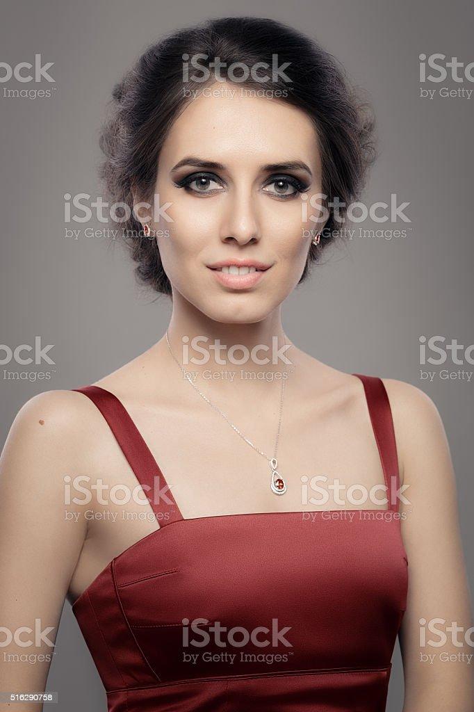 Beautiful Woman in Red Elegant Dress Wearing Ruby Jewelry stock photo