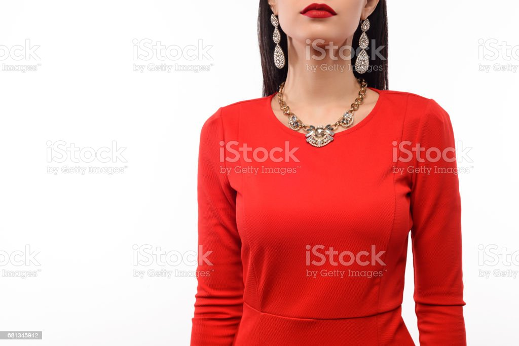 Beautiful woman in red evening dress with necklace and earrings. stock photo