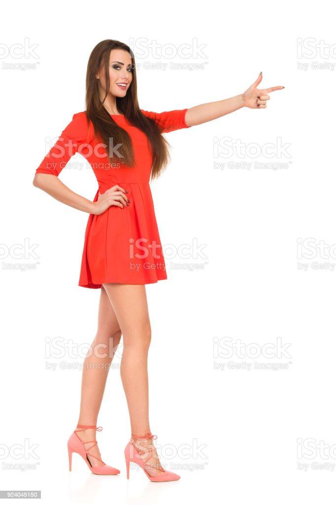 4a19816e2b5 Belle femme en robe Mini rouge et des talons hauts est pointé photo libre  de droits