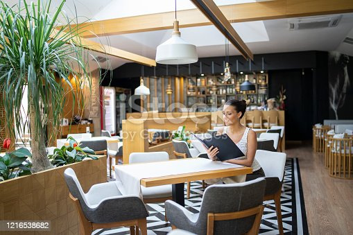 Beautiful woman sitting in reastaurant and reading menu