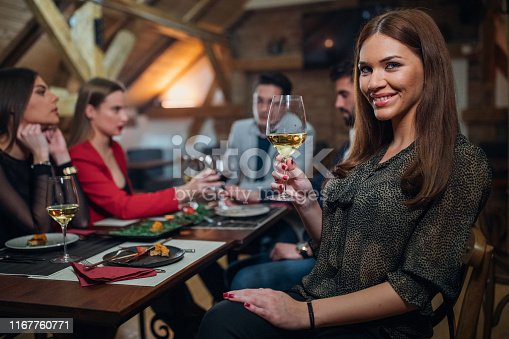 Group of people, men and women, sitting in restaurant together, beautiful woman holding wineglass.