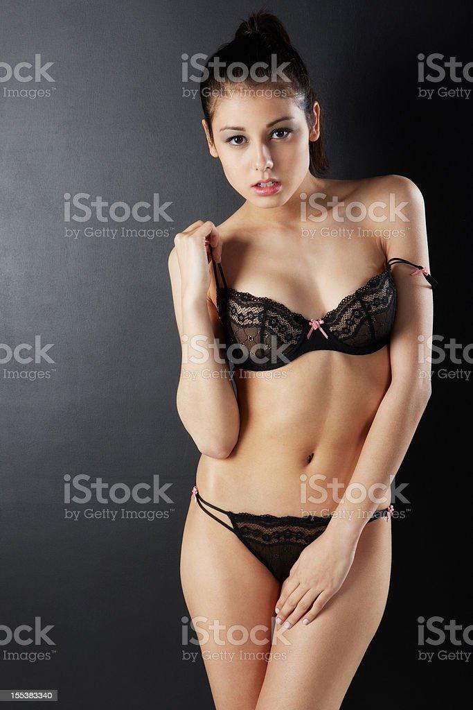 Schöne Frau In Sexy Dessous Hand Holding Bhträger Stock Fotografie