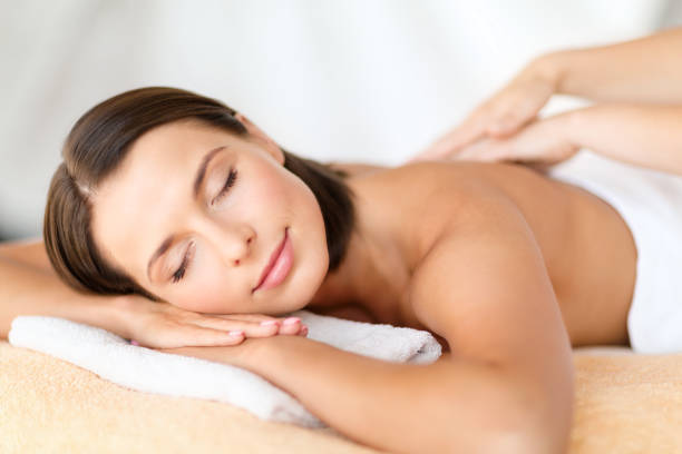 beautiful woman in spa salon getting massage health, beauty, resort and relaxation concept - beautiful woman with closed eyes in spa salon getting massage massaging stock pictures, royalty-free photos & images