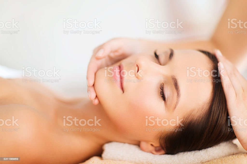 beautiful woman in spa salon having facial massage stock photo