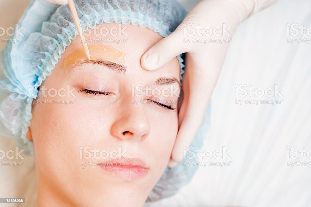 Beautiful woman in spa salon receiving epilation or correction eyebrow stock photo