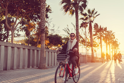 Beautiful woman in Spain riding a bicycle on sunset