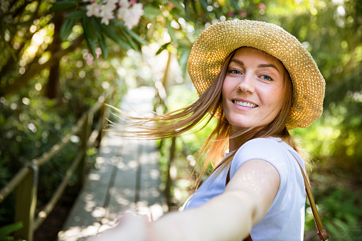 Beautiful woman in straw hat travel in tropic forest