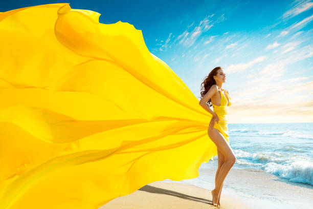 Beautiful Woman in Summer Sexy Dress on Sea Beach, Gown Cloth Waving Fluttering on Wind, Outdoor Portrait stock photo